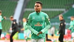 Werder-Spieler Felix Agu schaut nachdenklich beim Aufwärmen vor dem Spiel.