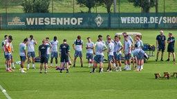 Werders Spieler und Trainer stehen auf dem Fußballplatz im Kreis.