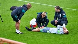 Christian Groß liegt ausgestreckt auf dem Rücken auf dem Trainingsplatz mit den Händen vor dem Gesicht und wird von Werder-Betreuern behandelt.