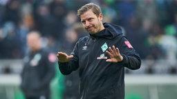 Florian Kohfeldt mit einer leicht abwehrenden Handhaltung, um zu signalisieren, den Ball flach zu halten.