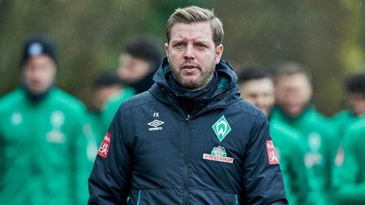 Florian Kohfeldt mit ernster Miene im Nieselregen auf dem Weg zum Trainingsplatz.