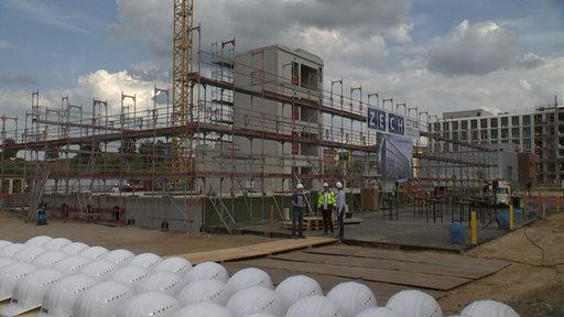Zu sehen ist eine Baustelle mit Gerüsten, auf der ein Haus gebaut wird.