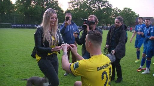 Ein Fußballspieler des Bremer SV macht seiner Freundin auf dem Spielfeld einen Heiratsantrag.