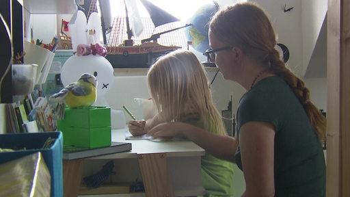 Ein Junge sitzt mit seiner Mutter am Schreibtisch und schreibt