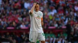 Kruse fasst sich mit gesenktem Kopf in die Haare während des Bayern-Spiels.