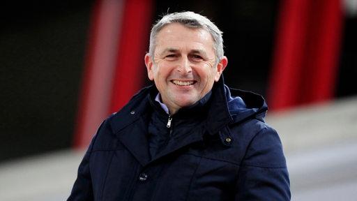 Klaus Allofs steht im Düsseldorfer Stadion und lächelt.