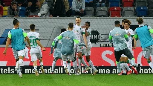 Werder-Spieler um Maximilian Eggestein feiern ausgelassen den ersten Saisonsieg.