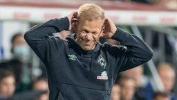 Werder-Trainer Markus Anfang verschränkt die Hände im Nacken und kneift die Augen zusammen.