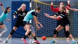Amateur-Handballerinen während eines Spiel. Ein Team greift an, das andere verteidigt. Die Torhüterin hebt bereits die Hände.