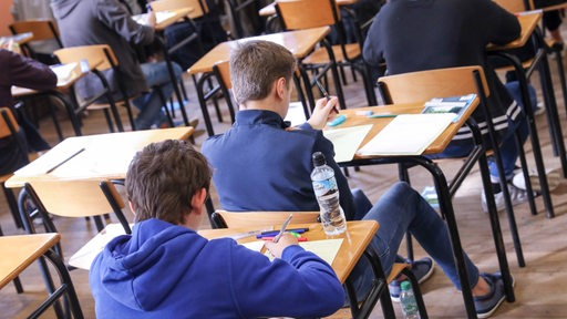 Schüler sitzen hintereinander an Tischen und lösen Aufgaben.