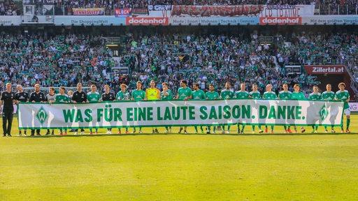 Die Werder-Spieler halten nach dem letzten Spieltag ein Banner am Mittelkreis hoch mit der Aufschrift