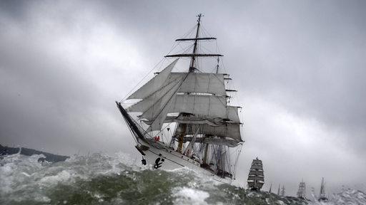 Das Segelschulschiff Gorch Fock fährt unter wolkigem Himmel durch aufgewühltes Wasser