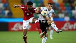 Zwei Fußballer kämpfen um den Ball.