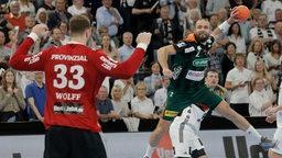 Torge Johannsen (Hannover) im Sprungwurf gegen Torwart Andreas Wolff (Kiel).