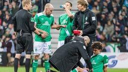 Die Mannschaftsärzte bei Werder kümmern sich um den verletzten Milos Veljkovic