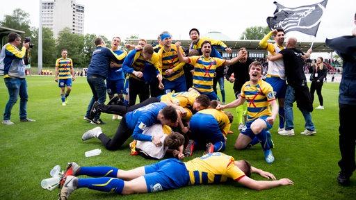 Die Spieler von Atlas Delmenhorst feiern auf dem Rasen ausgelassen den Einzug in den DFB-Pokal.
