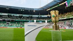 Der DFB-Pokal steht im Weser-Stadion neben einem Sprtschau-Tisch.