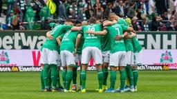 Die Werder-Mannschaft steht in einem Kreis zusammen mit geduckten Köpfen.