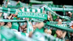 Werder-Fans halten auf der Tribüne ihre Fanschals hoch.