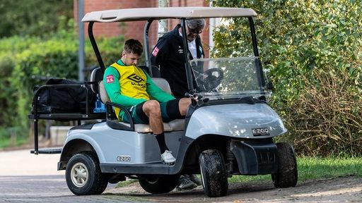 Niclas Füllkrug sitzt mit sinkendem Kopf im Golfcart.