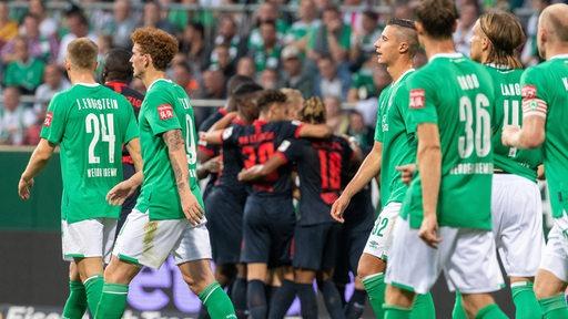 Während die Spieler von Leipzig ihren Treffer bejubeln, schauen die Werder-Profis enttäuscht drein.