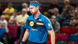 Timo Boll dreht sich enttäuscht nach einem Fehler von der Tischtennisplatte weg.