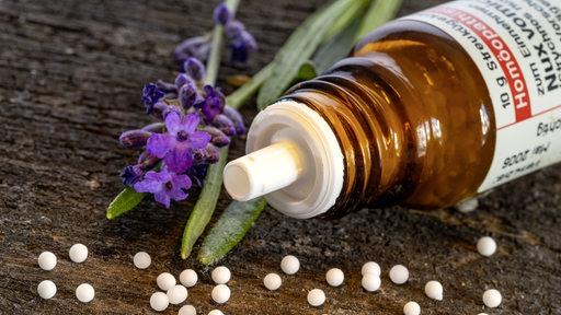 Weiße Kügelchen vor einer kleinen Flasche und eienr violetten Blume.