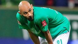 Ömer Toprak beugt sich während eines Spiels nachdenklich nach vorne und stützt die Hände auf die Oberschenkel.