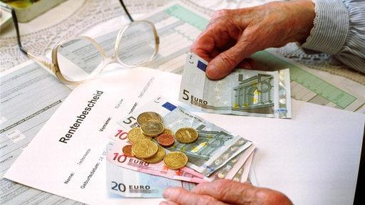 Frau zählt Geld auf einem Rentenbescheid.