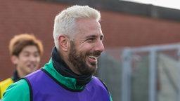 Claudio Pizarro strahlt beim Training mit frisch-blondierten Haaren und dunklem Bart.
