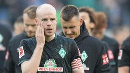 Davy Klaassen trottet gemeinsam mit Maximilian Eggestein nach der Niederlage vom Spielfeld und fasst sich dabei ins Gesicht.
