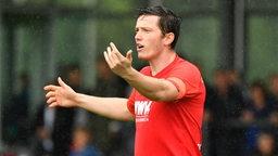 Der Augsburger Spieler Michael Gregoritsch steht im Regen auf dem Spielfeld und gestikuliert mit beiden Armen.