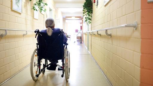 Alte Frau im Rollstuhl auf dem Flur eines Altenpflegeheims .