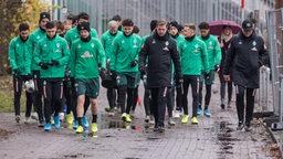 Die Werder-Mannschaft trottet mit Trainer Kohfeldt voran im Nieselregen zum Trainingsplatz.