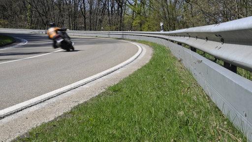 Motorradfahrer in einer Kurve auf einer Landstraße mit Leitplanke.