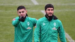 Milot Rashica legt im Training den Arm um Nuri Sahin und zeigt mit dem Zeigefinger in Richtung Kamera.