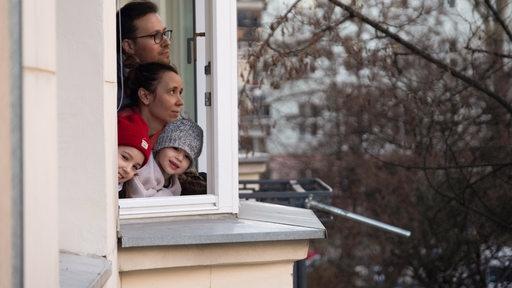Eine Familie mit Kindern schaut aus dem Fenster ihrer Wohnung (Symbolbild)