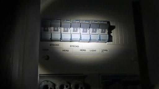 Ein Lichtkegel strahlt einen Schaltkasten an.