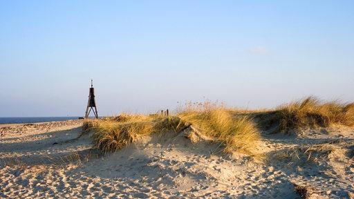 Blick auf einen Sandstrand. Im Hintergrund sind das Meer und das Cuxhavener Wahrzeichen, die Kugelbake, zu sehen.