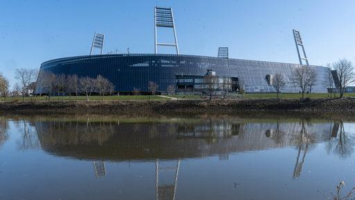 Blick aus der Ferne auf das Weser-Stadion im Sonnenschein, das sich in der Weser spiegelt.