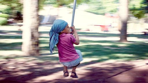 Ein Mädchen auf einem Spielplatz hängt an einer Seilbahn.