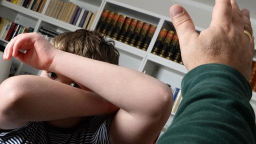 Ein Junge versucht sich vor den Schlägen seines Vaters zu schützen (gestelltes Bild).