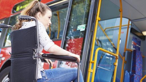 Eine Frau im Rollstuhl bereitet sich darauf vor, mit ihrem Rollstuhl in einen Bus zu fahren.