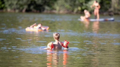 Ein Kind mit Schwimmflügeln in einem Badesee, im Hintergrund Badegäste mit Luftmatraze und beim Standup-Paddling (Symbolbild)