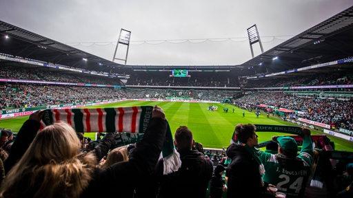 Werder-Fans halten im Weser-Stadion ihre Schals hoch.