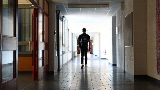 Ein einsamer Schüler geht einen leeren Schulflur entlang.