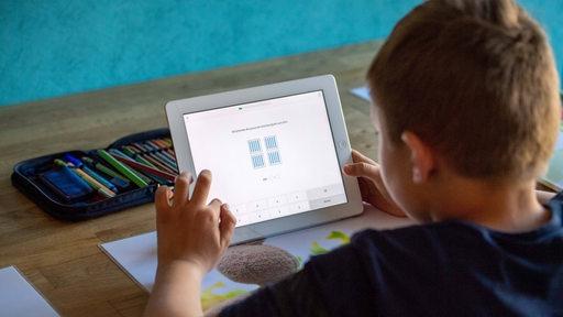 Ein Schüler löst zu Hause seine Schulaufgaben am Ipad,