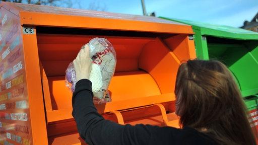 Eine Frau wirft einen Sack Altkleider in einen Container