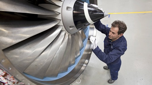 Ein Airbus-Mitarbeiter steht an einem Triebwerk in einer Montagehalle