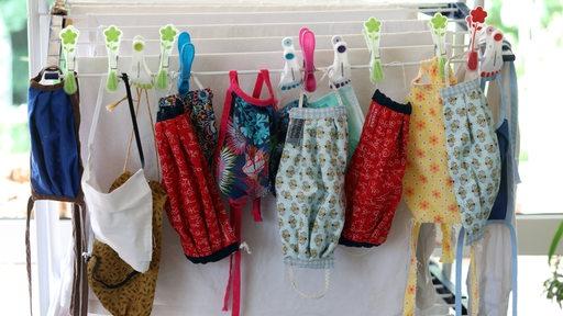 Mehrere Alltagsmasken hängen an einem Wäscheständer zum Trocknen.